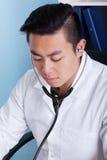 在的亚裔医生与听诊器一起使用期间 库存照片
