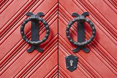 在的古色古香的金属门把手红色木门 库存图片