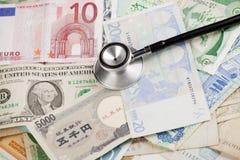 在的听诊器不同的钞票。 免版税库存照片