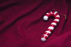 在的圣诞节藤茎垂悬的装饰品红色织品背景折痕  库存图片