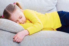 在的女孩睡眠在沙发的便衣 免版税图库摄影