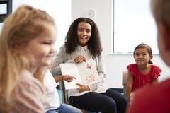 在的女老师显示图片的肩膀观点在书对一个小组幼儿园孩子坐在classr的椅子 免版税库存照片