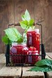 在的山莓果酱瓶子和叶子 库存照片