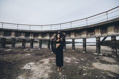 在的干的水坝的背景的美丽的女孩  图库摄影
