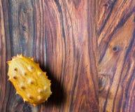 在的异乎寻常的kiwano果子左下一个木背景 免版税库存图片