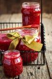 在的新山莓果酱在木桌上的瓶子 免版税图库摄影
