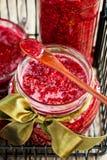 在的新山莓果酱有匙子的瓶子 图库摄影