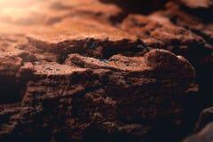 在的日落毁损被照亮的岩石表面 免版税库存照片