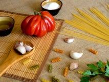 在的未煮过的干燥意粉土气表面用蕃茄,大蒜, 免版税库存图片