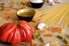 在的未煮过的干燥意粉土气表面用蕃茄,大蒜, 库存照片
