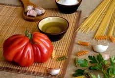 在的未煮过的干燥意粉土气表面用蕃茄,大蒜, 免版税库存照片