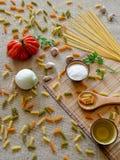 在的未煮过的干燥意粉土气表面用蕃茄,大蒜, 免版税图库摄影