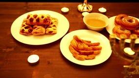在的桌上油炸圈饼在油,蛋糕,蜂蜜油煎了,并且芯片是menorah