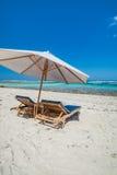在的沙滩伞铺沙与太阳懒人椅子 免版税库存照片