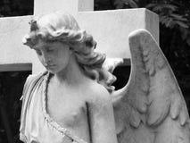 在的白色大理石天使与十字架的坟茔 免版税库存照片