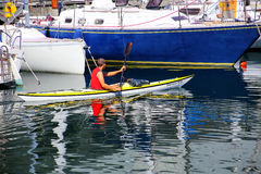 在的里雅斯特小游艇船坞,意大利供以人员划皮船沿小船 免版税图库摄影