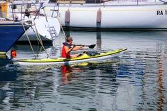 在的里雅斯特小游艇船坞,意大利供以人员划皮船沿小船 免版税库存照片