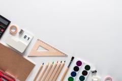 在的顶视图笔记本,油漆,铅笔,统治者,纸夹,别针, stepler,胶浆,磨削器,笔,在白色背景的纸 库存图片