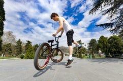 在的bmx骑自行车者下跳跃反对天空的观点 免版税库存图片