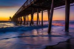 在皇家海滩,加利福尼亚的日落以后被看见的渔码头 免版税库存图片