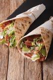 在皮塔饼和莴苣包裹的烟肉在特写镜头上添面包 垂直 免版税图库摄影