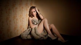 在皮大衣包裹的可爱的性感的少妇坐在旅馆客房 肉欲的哀伤的女性画象  免版税库存图片