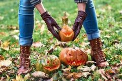 在皮手套的妇女手拿着一个万圣夜南瓜室外在秋天公园 免版税库存照片