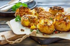 在皮肤的被烘烤的土豆用香料、橄榄油和大蒜 库存照片