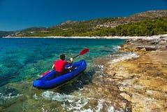 在皮船的人划船在亚得里亚海 免版税库存照片