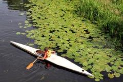 在皮船的男孩浮游物在河下 免版税图库摄影