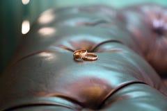在皮革沙发的两只金戒指 图库摄影