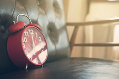 在皮革沙发的减速火箭的闹钟 免版税库存照片