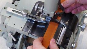 在皮革磨的机器的人工作 使用成斜面边缘和分裂皮革小条到各种各样的厚度为 影视素材