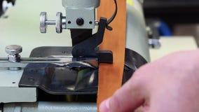 在皮革磨的机器的人工作 使用成斜面边缘和分裂皮革小条到各种各样的厚度为 股票录像