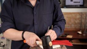 在皮革空白,一个人做与锤子和一个特定工具的孔 股票视频