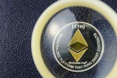 在皮革纹理的金黄ethereum谎言在放大器玻璃下 库存图片