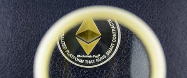 在皮革纹理的金黄ethereum谎言在放大器玻璃下 免版税库存图片