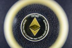在皮革纹理的金黄ethereum谎言在放大器玻璃下 免版税图库摄影