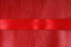 在皮革背景的发光的红色丝带条纹。 库存图片