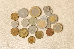 在皮革背景的很多疏散硬币 免版税库存图片