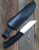 在皮革鞘附近的钢猎刀 免版税库存图片