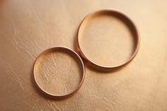 在皮革黄色背景的两个婚戒 免版税图库摄影