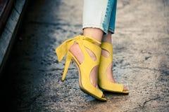 在皮革黄色高跟鞋凉鞋的妇女腿室外在城市 图库摄影