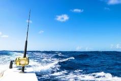 在盐水小船的钓鱼竿在渔场天期间在蓝色海洋 成功的渔概念 免版税图库摄影