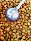在盐水的布朗深绿被治疗的橄榄辣椒葱与杓子 发光的光滑的纹理 健康地中海饮食西班牙意大利 免版税库存图片