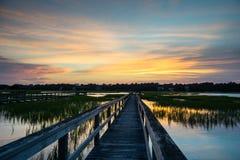 在盐沼的木木板走道在日落期间 图库摄影
