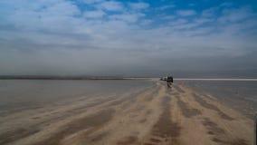 在盐湖Karum湖Assale或Asale日落的,在远处Danakil的亦称汽车,埃塞俄比亚 库存照片