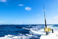 在盐水小船的钓鱼竿在渔场天期间在蓝色海洋 免版税库存图片