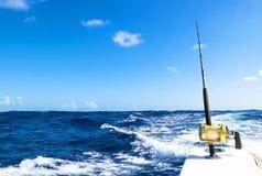 在盐水小船的钓鱼竿在渔场天期间在蓝色海洋 图库摄影
