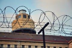 在监狱墙壁附近的铁丝网篱芭 免版税库存照片